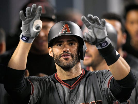 Arizona Diamondbacks' J.D. Martinez gestures toward the camera as he stands in the dugout after hitting his fourth home run of the game in the ninth inning of a baseball game against the Los Angeles Dodgers, Monday, Sept. 4, 2017, in Los Angeles. Martinez tied a major league record by slugging four of Arizona's six home runs, and the Diamondbacks routed the NL West-leading Los Angeles Dodgers 13-0 on Monday night for their 11th straight victory. (AP Photo/Mark J. Terrill)