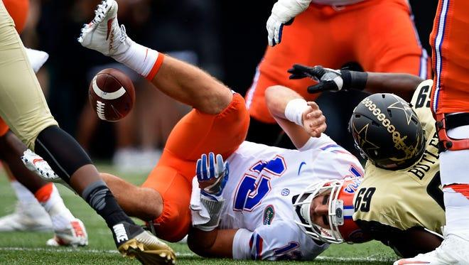 Florida quarterback Austin Appleby (12) loses the ball after being hit by Vanderbilt defensive lineman Adam Butler (69) in first half action at Dudley Field Saturday, Oct. 1, 2016, in Nashville, Tenn.