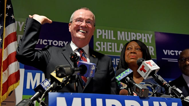 "Democratic gubernatorial nominee Phil Murphy ""raises the roof"" while formally announcing Sheila Oliver as his running mate during a July press conference in Newark."
