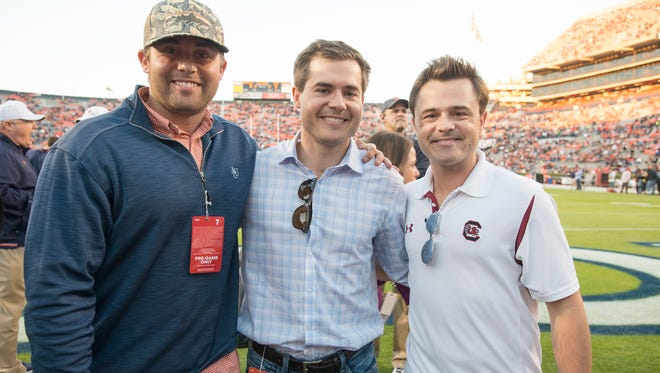 Brothers Perry Hooper, Davis Hooper and Thomas Hooper stand on the field before the NCAA football game between Auburn and South Carolina on Saturday, Oct. 25, 2014, in Auburn, Ala. Perry and Davis are former Auburn players and Thomas played for South Carolina.
