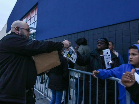 Computer manager Rod Chambers passes out sales circulars to shoppers in line at Best Buy's Black Friday event on Nov. 24, at Christiana Fashion Center in Newark.