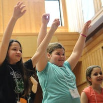 Aubrey Menard, 10, of Iberia Parish; Blair Little, 9, of St. Landry Parish; and Juliana Carbalan, 10, of Jefferson Davis Parish, take a big stretch during the recent Louisiana 4-H Food and Fitness Camp.