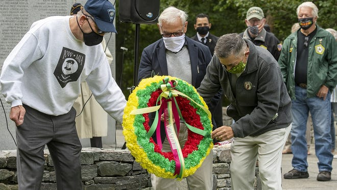 Steven Bott of Millbury, former POW Joseph Rovezzi, and Harry Kustigian of Leicester, left to right, place a POW/MIA wreath during the National POW/MIA Recognition Day ceremony at the Massachusetts Vietnam Veterans' Memorial in Green Hill Park in Worcester Friday.