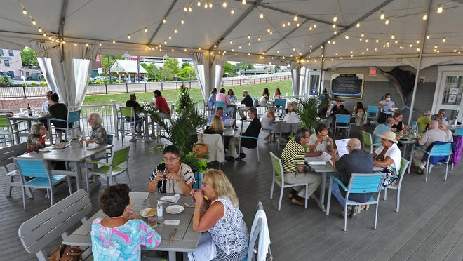 Diners enjoy their meals under the canopy tent at The Black Whale  Resturant on Pier 3 in New Bedford.