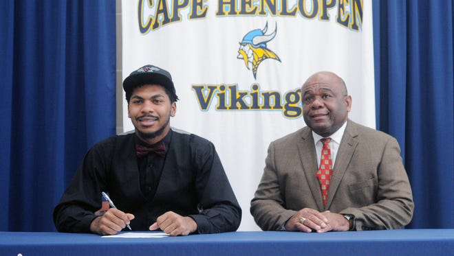 Cape Henlopen senior Michael Williams, accompanied by Cape head coach Bill Collick, signs his national letter of intent to play football at Delaware State University.
