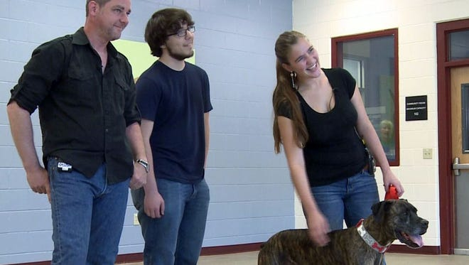 From left, Lloyd Goldston, left, and his children are reunited with their dog, Boozer, after a 9-year separation, in Golden, Colo. Boozer, now 10, went missing while the family was moving from Tennessee to Alabama.