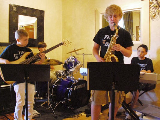 Time Out, a quartet of local teens, rocks at Serenity Station in Seven Valleys. Two of the group members, Cole (on bass guitar) and Hayden (on saxophone), are heading to Germany this summer to raise funds so the whole group can make the trip in 2011.