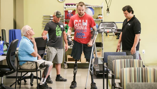 Triple amputee Christopher Allen McCoy, center, learns new exercises to help him with everyday activities during a session of Amputee Walking School at the IU Health Neuroscience Center in Indianapolis on Monday, April 17, 2017. Left to right:  Fred Pridgen, Brandon Anderson, Christopher Allen McCoy, Todd Schaffhauser.