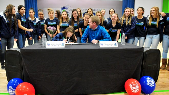 Keira Richards signs a letter of intent for the the University of Providence women's soccer team as the the Lady Argos soccer team and their coach, Brian Clarke, look on Wednesday afternoon in the McLaughlin Center.