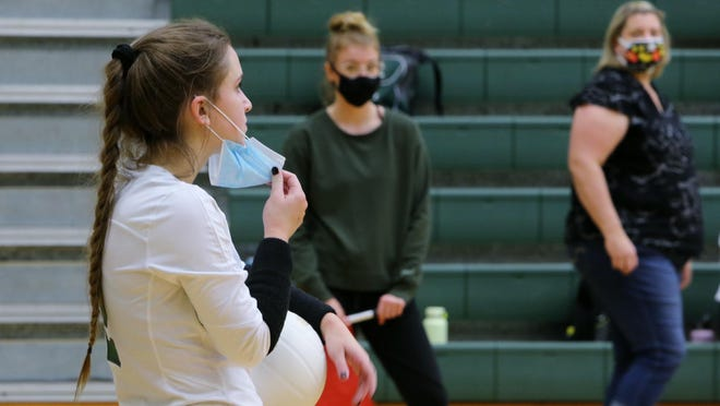East Henderson's Emma Gilliam takes her mask away from her face to take a breather prior to serving during Monday's match against Brevard.