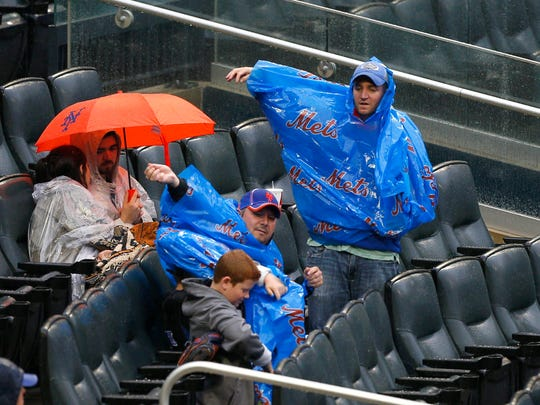 New York Mets fans put on rain gear during second of game against Toronto Blue Jays at Citi Field.