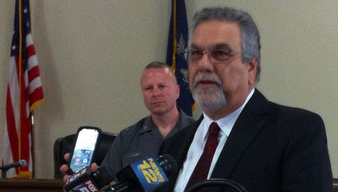 Robert L. Pavone, chairman of New York State Crime Stoppers, discusses a new program offering rewards for tips on heroin dealers on June 10, 2014, at the Richard J. Daronco Town House in Pelham. In the background is Capt. John Ryan of New York State Police Troop K.