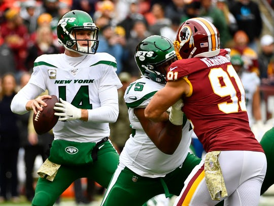 Nov 17, 2019; Landover, MD, USA; New York Jets quarterback Sam Darnold (14) prepares to throws the ball as Washington Redskins outside linebacker Ryan Kerrigan (91) rushes during the first half at FedExField. Mandatory Credit: Brad Mills-USA TODAY Sports
