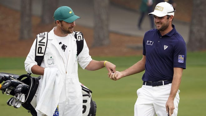 Corey Conners gets his ball back from caddie Kyle Peters on the second green Sunday during the final round of the Masters Tournament. The Canadian will be back for the 2021 tournament after finishing in a tie for 10th.