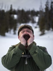 Biologist Ken Mills howls to a nearby collared wolf,