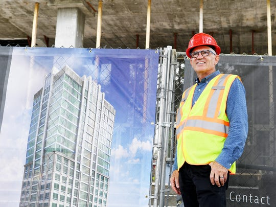 John McKibbon, chairman of McKibbon hospitality, which is the developer of the Arras building, stands next to a rendering of the building June 13, 2017.