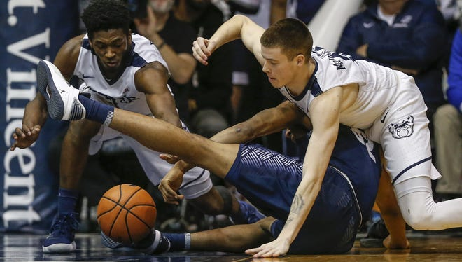 Butler Bulldogs guard Sean McDermott (22) fights for a loose ball with Georgetown Hoyas guard Kaleb Johnson (32) at Hinkle Fieldhouse on Tuesday, Feb. 13, 2018.