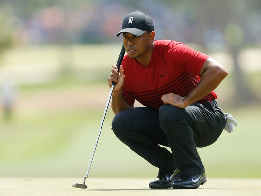 Tiger Woods looks over a putt on the second green during