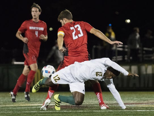 Vermont's Bernard Yeboah (12) gets tripped up as he