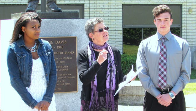 Ernie Davis Scholarship committee member Donna Homuth, center, introduces scholarship winners Taylor Jubilee, left, and Owen Mason on Thursday in front of the Ernie Davis statue at the former Ernie Davis Middle School in Elmira.