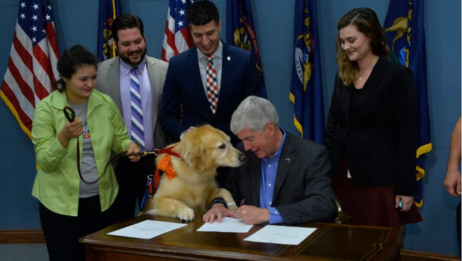 This photo provided by the Michigan House Republicans shows state Rep. Tom Barrett, third from left, standing with legislative staff, a bill supporter  and a service dog as Gov. Rick Snyder signs Barrett's bill creating service dog registration on Oct. 20, 2015.