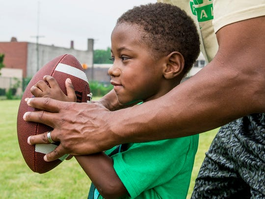 Assistant coach Desmond Shaw of Dacula, Ga. shows Joshua Dasgupta, 5, of Southfield how to prepare to run a play as quarterback.