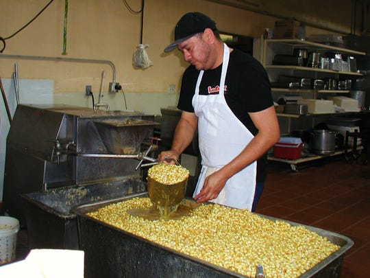 Noel Lopez feeds hominy into a machine where the corn is ground to make masa.