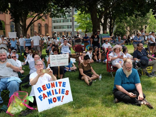 People attending the Families Belong Together rally at the state Capitol in Lansing on Saturday, June 30, 2018 seek out the shade to escape temperatures in the mid-90s.