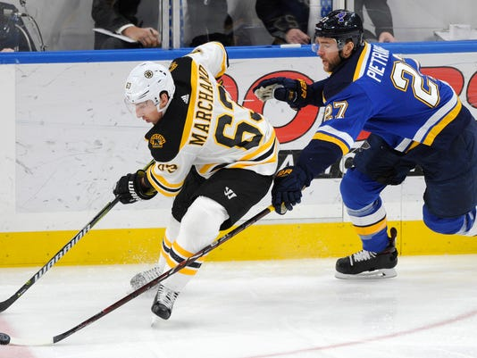St. Louis Blues' Alex Pietrangelo (27) and Boston Bruins' Brad Marchand (63) reach for the puck during the first period of an NHL hockey game Wednesday, March 21, 2018, in St. Louis. (AP Photo/Bill Boyce)