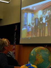 Becky Shady and a room full of guests watch as Orland, Norway, Mayor Tom Myrvold holds up his signed copy of the Sister Cities agreement  in 2017.