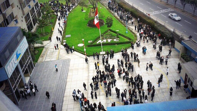 People gather in front of an office complex in Lima, during an earthquake that struck off Peru's southern coast.