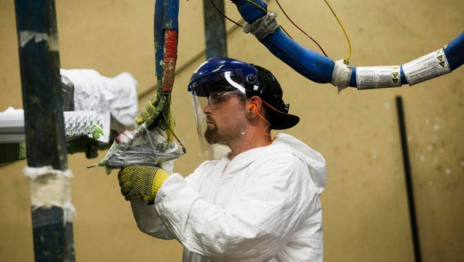 A worker assembles construction supplies at Northeast Building Products in Philadelphia in August 2014.