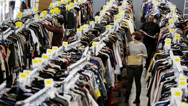In this photo taken Wednesday, April 9, 2014, workers locate and pull items for shipping from racks of designer clothing at the headquarters of The RealReal in San Francisco.