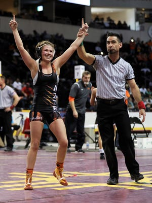 ​Aztec's Bella Wells celebrates her state championship win over Sandia's Tiana Ring in the girls 106-pound state championship match Saturday at the Santa Ana Star Center in Rio Rancho.