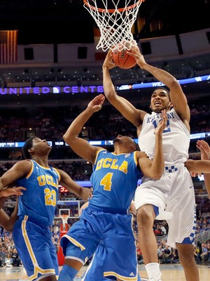 REMOVES REFERENCE TO NORTH CAROLINA IN SECOND SENTENCE - Kentucky forward Karl-Anthony Towns (12) grabs a rebound over UCLA forward Tony Parker (23) and Norman Powell, during the first half of an NCAA college basketball game Saturday, Dec. 20, 2014, in Chicago. (AP Photo/Nam Y. Huh)