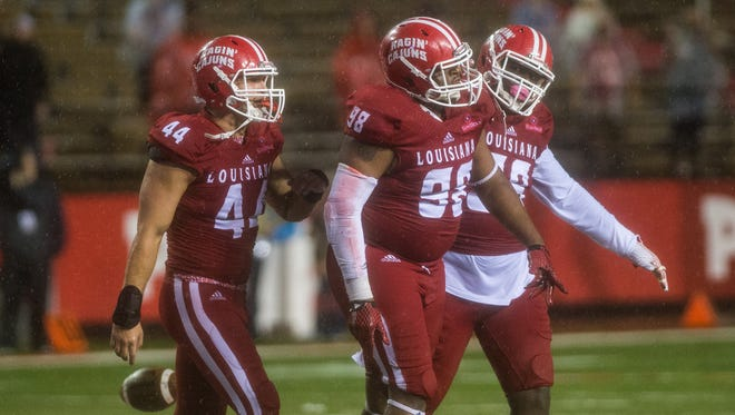 UL defensive lineman LaDarrius Kidd (98), center, celebrates with teammates after recovering a fumble late in the fourth quarter against UL Monroe last season.