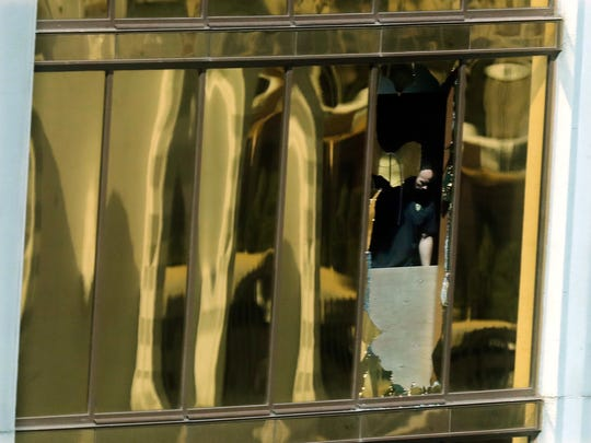 An investigator works in the room at the Mandalay Bay Resort and Casino where a gunman opened fire from on a music festival Tuesday, Oct. 3, 2017, in Las Vegas. The gunman killed dozens and injuring hundreds at the festival. (AP Photo/Marcio Jose Sanchez)