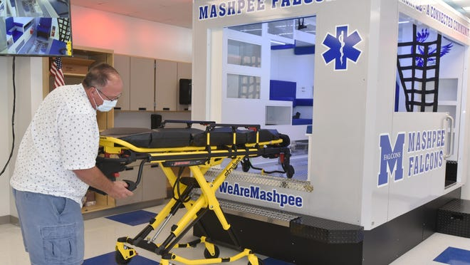Michael Looney, director of Mashpee Middle-High School's Career and Technical Education department, operates a cot on the new ambulance simulator obtained through a grant to train students interested in the medical field.