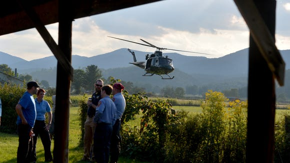 A helicopter takes off near search team members who wait for their turn to join the search for a missing pilot at the mobile command center at the Deerfield Volunteer Fire Department on Wednesday, August 27, 2014. They search for the missing pilot of an F15c fighter jet which crashed into a mountain near Elliot Knob in Augusta County.