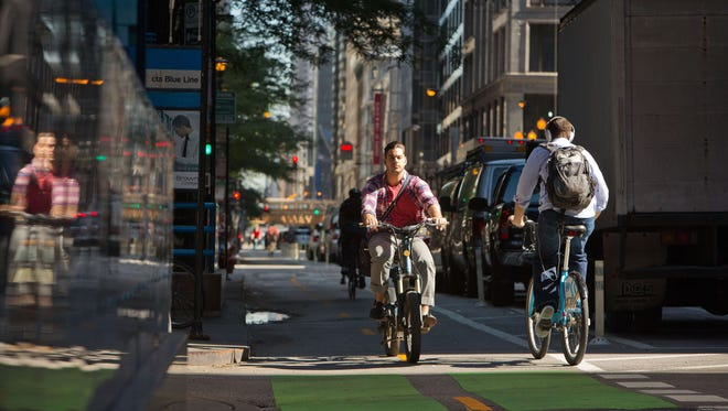 A cyclist travels south on Dearborn Street near Jackson Boulevard during the morning rush hour in Chicago on  July 11.