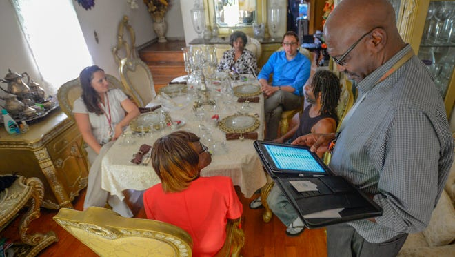 Donnie Missouri takes notes while Kristan Halaiko, Lisa Brown and Joe Martenczuk listen during a home visit with clients Donney Jefferson and his fiancée, Rosaleita Fulford. They are part of a  team from Johns Hopkins that goes out into the community to follow up with super-utilizers.