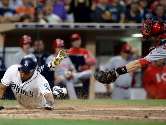 APTOPIX San Diego Padres' Yangervis Solarte, left, slides by the tag attempt by Cincinnati Reds catcher Devin Mesoraco to score on a single to center field by Cory Spangenberg during the fifth inning of a baseball game in San Diego, Tuesday, June 13, 2017. (AP Photo/Alex Gallardo)
