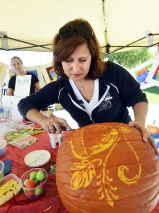 Allison Zeger, with the Mercersburg Council for the Arts, carves pumpkins at Mercersburg TownFest on Saturday, September 27, 2014.