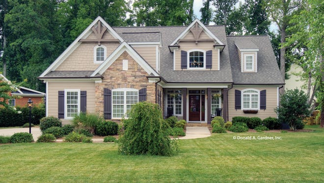 Shown modified here with a side-facing garage, the exterior exudes cottage charm with stone siding and dormer windows.