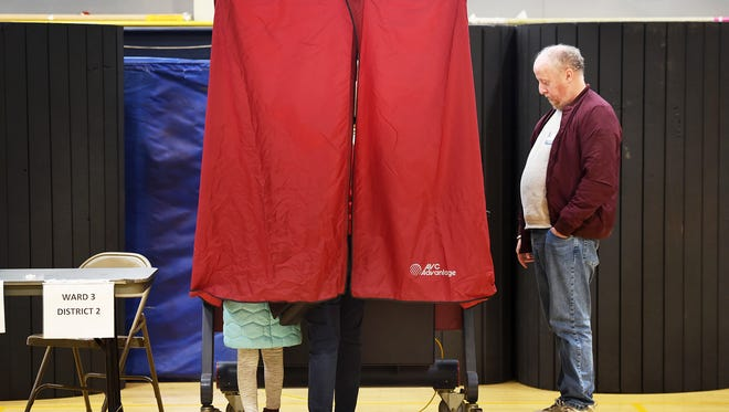A voter accompanied by a young girl casts her vote at the Hackensack High School gym on Nov. 7, 2017.