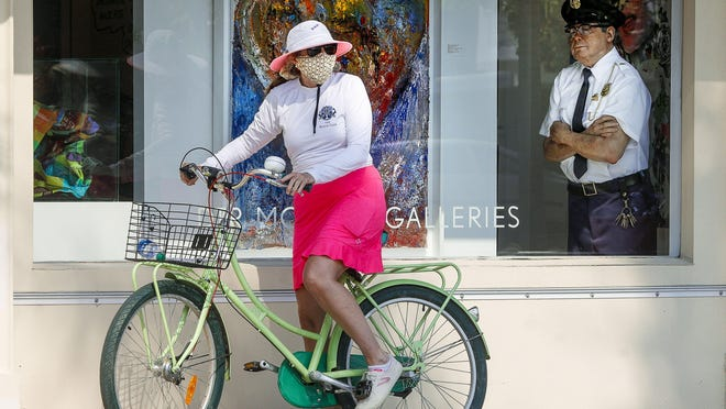 Maggie Rooney wears a mask in April as she prepares to begin exercising again on her bike after taking a brief pause to rest in front of DRT Modern Galleries as a work of art that looks like a real live police officer watches her from behind through the gallery's window.