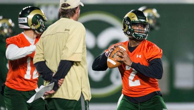 CSU redshirt freshman quarterback Justice McCoy (2) throws while head coach Mike Bobo watches during a practice earlier in spring.