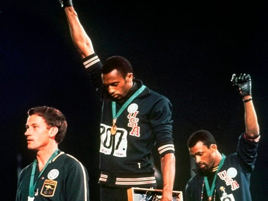 Americans Tommie Smith, center, and John Carlos raised their gloved fists in protest during the 1968 Olympics.