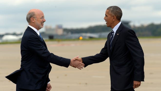 President Barack Obama, right, reaches out to shake hands with Pennsylvania Gov. Tom Wolf, left, after arriving at Pittsburgh International Airport in Pittsburgh, Thursday, Oct. 13, 2016.