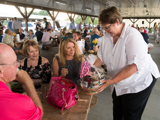 Susan Edwards, right, delivers a gift basket from Stone Hill Honey to Janet Faught, middle, during the Farm to Table event held at the Henderson County Fairgrounds Monday evening.